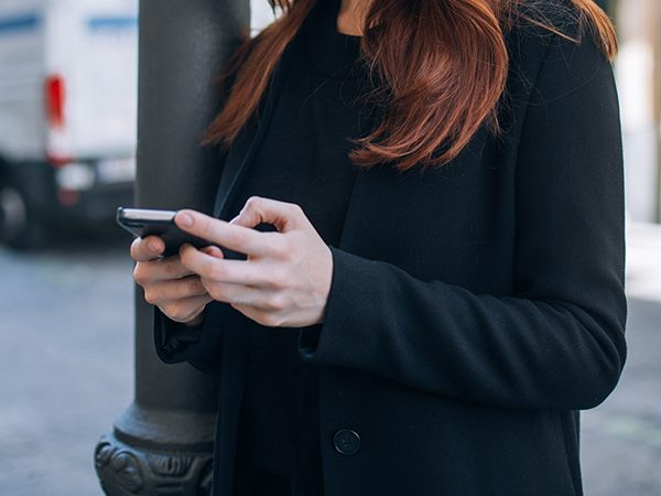 Beautiful casual woman with red hair and natural makeup stands on street and texts or chats on her smartphone, connects with friends and family, vertical mobile screen verison